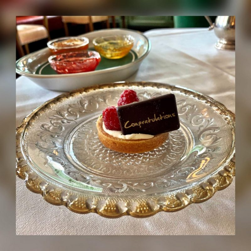 Mini pastry case filled with cream, 3 raspberries and a dark chocolate sign with Congratulations written on it in gold