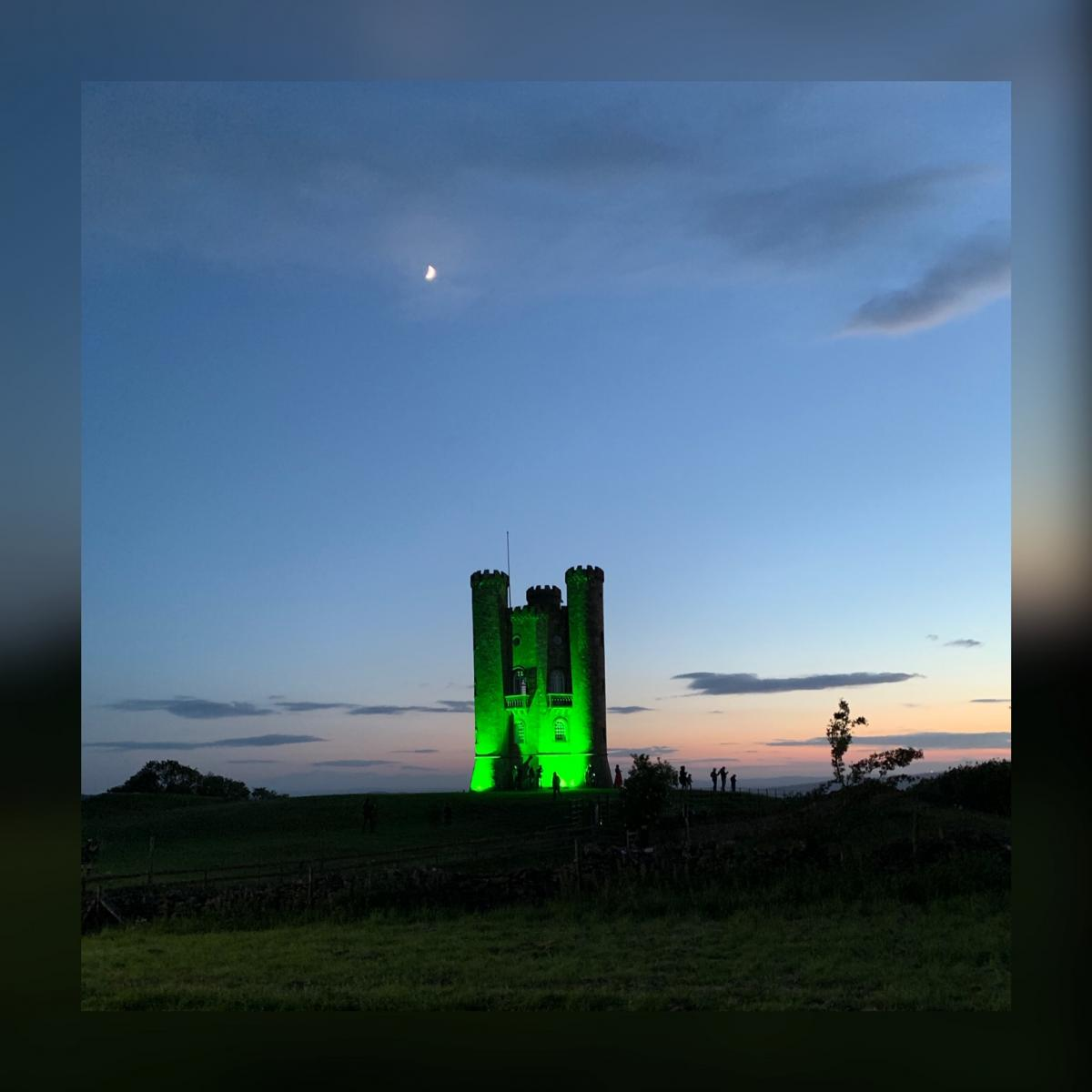 Broadway Tower lit up in Heineken Green with the moon and sunset in the background