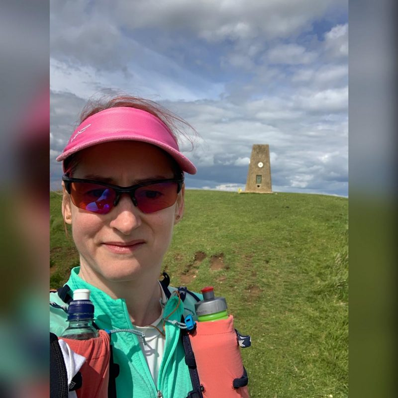 Kat takes a selfie in front of the Cleeve Common trig point