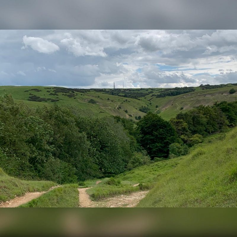 View of the Cotswold Way coming down to Postlip Hall